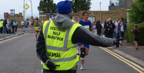 A marshal directs runners around the final turn in the Southend Half-marathon