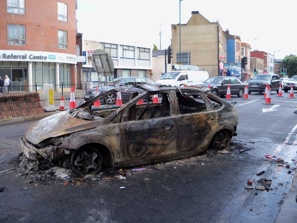 A burnt-out police car in Tottenham after the first night of riots in London